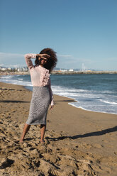 Young woman with afro hairdo standing on the beach - MAUF01515
