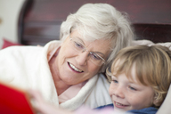Grandmother and grandson reading storybook in bed - CUF42936