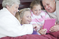 Grandparents and grandchildren playing digital game in bed - CUF42939