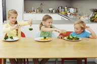 Girls scooping vegetables onto boy's plate - CUF42969