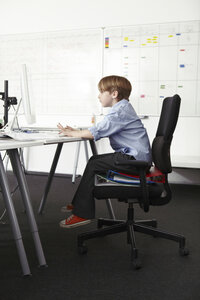 Boy sitting on ring binders on office chair using computer - CUF42984