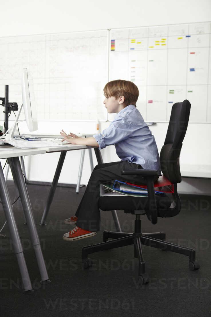 Boy sitting on ring binders on office chair using computer - CUF42984 - Emma Kim/Westend61