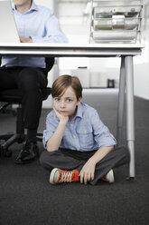 Boy sitting on floor with businessman working at desk - CUF42999