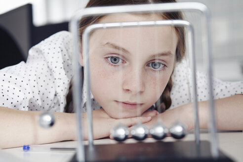 Girl playing with newton's cradle on desk - CUF43005