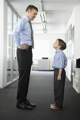 Father and son standing face to face in office - CUF43008