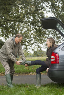 Senior couple taking off boots whilst out - CUF43137