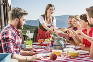 Group of friends at breakfast outside chalet, Tyrol, Austria - CUF43143