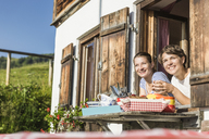 Two female friends looking out of chalet window, Tyrol, Austria - CUF43146