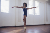 Graceful young female dancer practicing in dance studio - HOXF03620