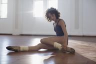 Focused, strong young female dancer stretching leg in dance studio - HOXF03629