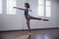 Graceful young female dancer practicing in dance studio - HOXF03638