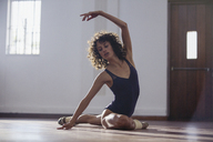 Graceful young female dancer stretching in dance studio - HOXF03665