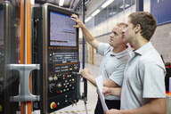 Workers looking at computer monitor in engineering factory - CUF43402