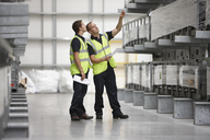 Warehouse workers checking shelves in engineering warehouse - CUF43414