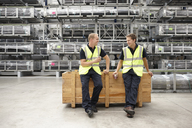 Two warehouse workers leaning on crate in engineering warehouse - CUF43417