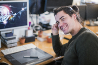 Portrait smiling, confident male graphic designer working at desk - CAIF20989