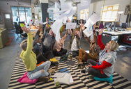 Playful, enthusiastic creative business team throwing paperwork overhead in open plan office - CAIF21043