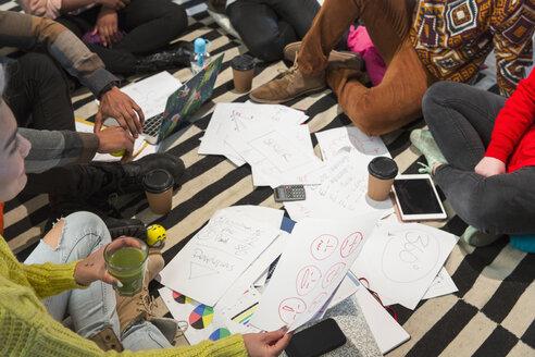 Creative business people meeting, brainstorming in circle on floor - CAIF21046