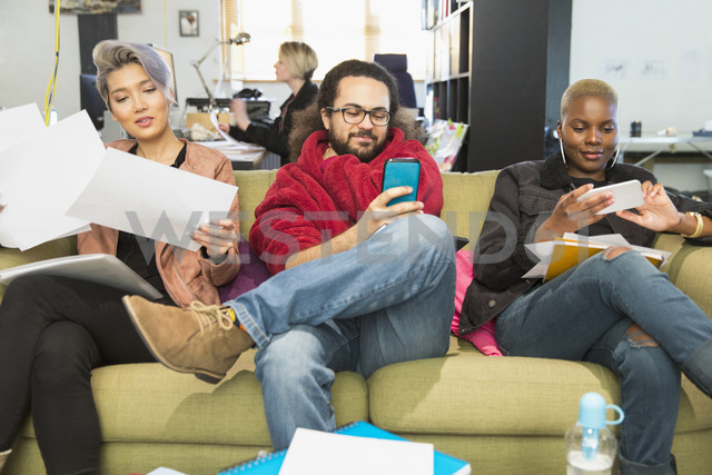 Creative business people using smart phones in office - CAIF21052