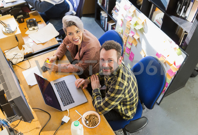 Portrait smiling, confident creative business people eating cereal, working at laptop in office - CAIF21067