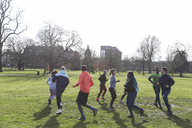 Runners jogging in circle in sunny park - CAIF21118