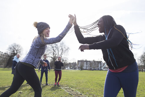 Enthusiastic women high-fiving, exercising in sunny park - CAIF21157