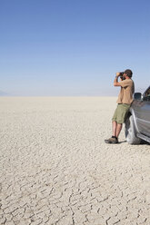 A man standing in a dry desert, looking through binoculars and leaning against a truck - MINF00072