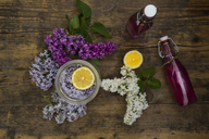 Two glass bottles of homemade lilac sirup and ingredients on wood - LVF07298