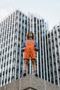 Beautiful woman wearing dungarees, standing on ledge in front of modern high-rise building - KKAF01218