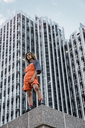 Beautiful woman wearing dungarees, standing on ledge in front of modern high-rise building - KKAF01221