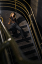 Stylish young woman sitting on stairs at night - KKAF01236