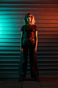 Stylish young woman at night in front of roller shutter - KKAF01239