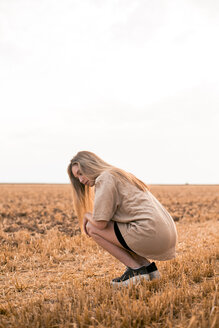 Young woman crouching on field - ACPF00119