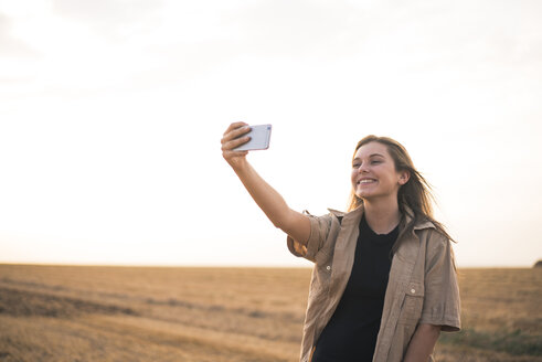 Young woman standing in field, making smartphone selfie - ACPF00125