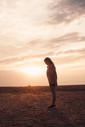 Lonely young woman standing on field at sunset - ACPF00128