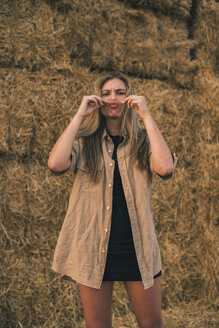 Young woman standing in front of hay bales making moustache with her hair - ACPF00131