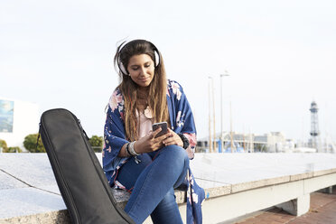 Spain, Barcelona, portrait of woman with guitar case and headphones looking at cell phone - JNDF00001