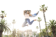 Spain, Barcelona, portrait of smiling young woman with headphones jumping in the air - JNDF00004