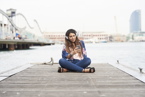Spain, Barcelona, portrait of content woman with headphones sitting on jetty looking at cell phone - JNDF00007