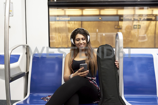 Portrait of smiling woman with guitar  and headphones looking at cell phone in underground train - JNDF00013