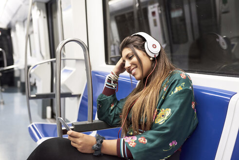 Smiling young woman listening music with headphones and smartphone in underground train - JNDF00016