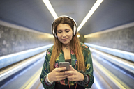 Portrait of woman with headphones looking at cell phone in underground station - JNDF00019