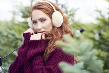 Portrait of redheaded young woman with freckles wearing ear muff and knit pullover - ABIF00700
