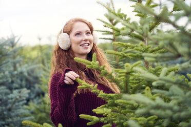 Portrait of smiling redheaded young woman wearing ear muff choosing Christmas tree at tree nursery - ABIF00706