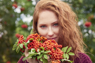 Portrait of freckled redheaded young woman with rowanberries - ABIF00712
