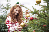 Portrait of redheaded young woman decorating Christmas tree outdoors - ABIF00715