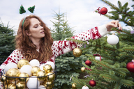 Redheaded young woman decorating Christmas tree outdoors - ABIF00718