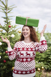 Portrait of laughing young woman balancing Christmas present on her head - ABIF00721