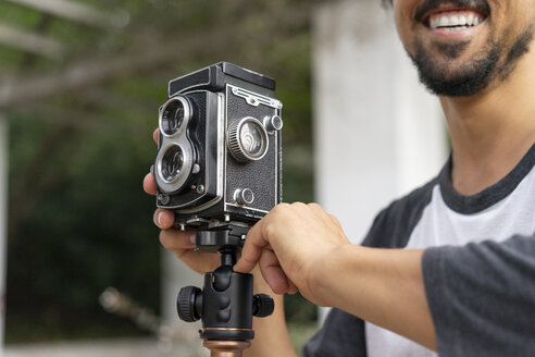 Close-up of happy young man using vintage camera - AFVF00803