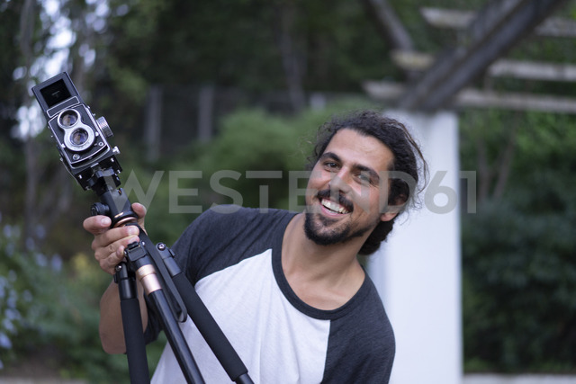 Portrait of happy young man with vintage camera - AFVF00806